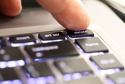 close up of a finger hitting pushing the delete symbol button tab on an illuminated laptop computer key board. The delete key