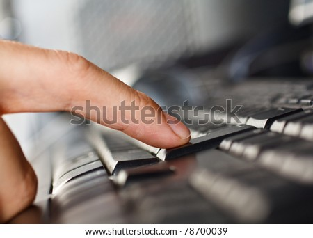 Close-up of a finger pressing the enter button - stock photo