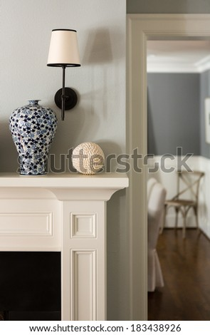 Close up of a fireplace mantle with a vase and lighting fixture.