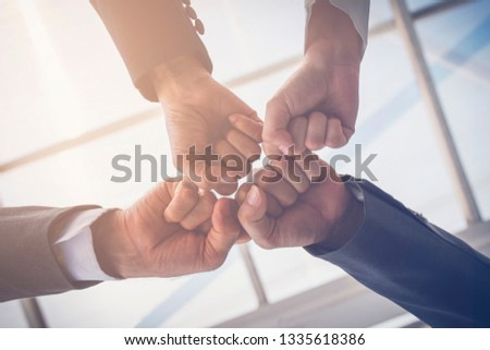 Close-up of a fist bump in vintage tone. Group hands of young people show strength teamwork. Business and teamwork concept.  #1335618386