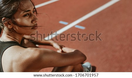 Close-up of a fit woman after run sitting on race track. Determined female athlete sitting on the field and looking away. Photo stock ©