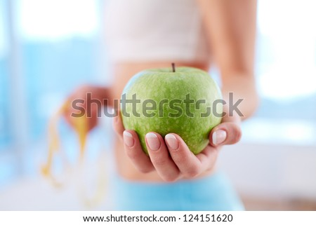Close-up of a fit woman holding a fresh apple