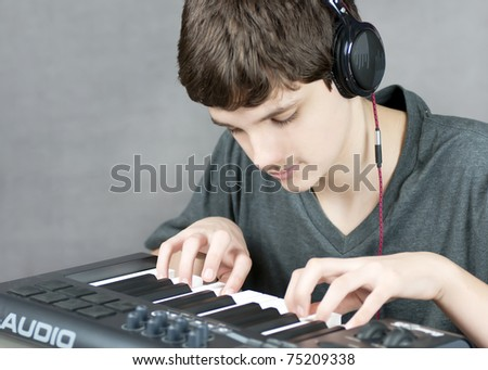 Close-up of a focused teen playing his keyboard.