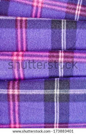Close up of a folded tartan blanket