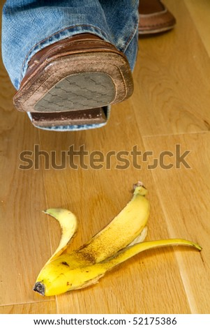 Close up of a foot about to tread on a banana skin