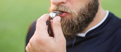 Close up of a football referee's whistle in his mouth