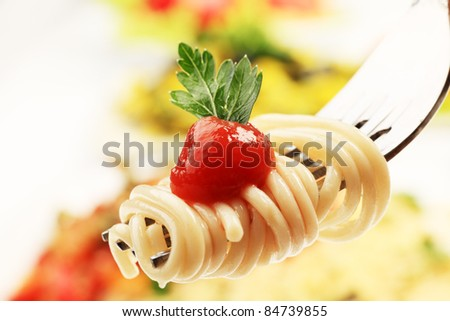 Close-up of a fork with spaghetti over pasta dishes.