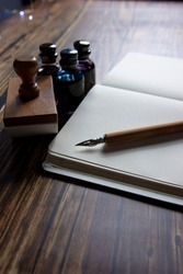 Close-up of a fountain pen on a notebook and several inkwells. Concept of writing poetry. International Poetry Day