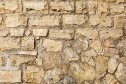 Close-up of a fragment of an old natural white limestone wall.