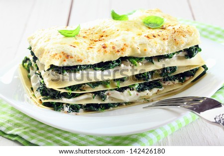 Close-up of a fresh baked vegetarian spinach lasagna on a plate, with a fork and over a napkin and an old white wooden table