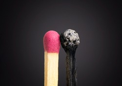 Close-up of a fresh unused matchstick close to a burnt one on a black background.