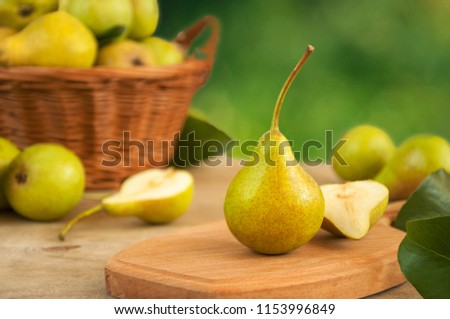 close-up of a fresh yellow pear on a wooden table in the background of a basket with pears and pears. #1153996849