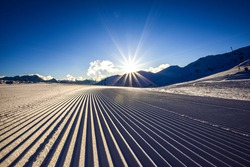 Close up of a freshly prepared skiing slope in the evening sun in the Zillertal skiing area in Austria, Europe. The piste is prepared with a snow grooming machine to ensure perfect conditions.