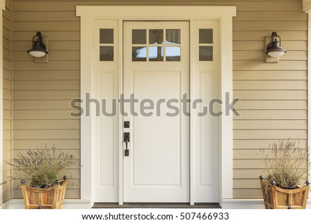 Close up of a front door with small square decorative windows and flower pots #507466933