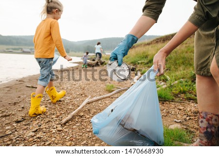 Close-up of a garbage collector by the river.  Family eco tourism. Environmental pollution. Ecological problem. #1470668930