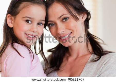 Close up of a girl and her mother smiling at the camera - stock photo