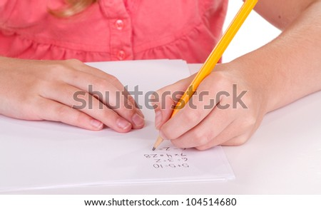 Close-up of a girl doing math problems on white paper