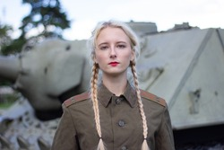close-up of a girl in a military uniform on the background of a tank