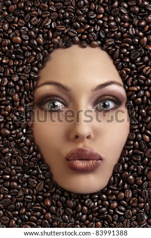 close up of a girl's face drowned in coffee beans blowing a kiss