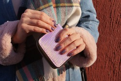 Close-up of a girl's hand with a lilac manicure holding an iridescent lilac wallet. Girl in winter clothes in pastel colors on the brown wall background. Walk on a sunny day