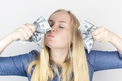 Close-up of a girl sniffing money. Madness and greed from currency. The concept of corruption and getting money at any cost. Squeeze and toss US dollars. Wild thirst for profit