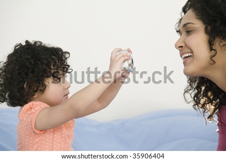 Close-up of a girl taking a picture of her mother with a digital camera