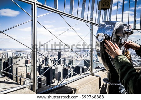 Close up of a girl that looks manhattan by telescope, from the Empire State Building #599768888