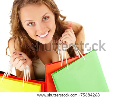 Close-up of a girl with paper bags looking at camera and smiling