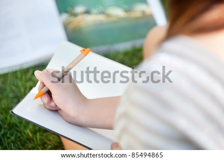 Close-up of a girl writing in a notebook
