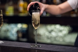 close-up of a glass of champagne poured from a bottle.