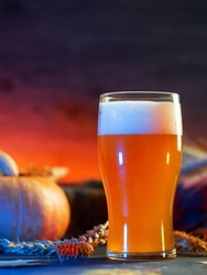 Close-up of a glass of craft pumpkin ale on an orange backlit background . Seasonal traditional beer for Thanksgiving or Oktoberfest