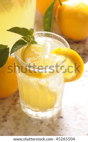 Close up of a Glass of Lemonade on counter in front of window with pitcher and lemons vertical format shallow DOF High angle