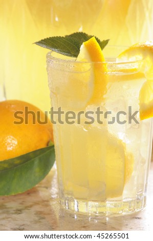 Close up of a Glass of Lemonade with pitcher and lemon behind vertical format shallow DOF
