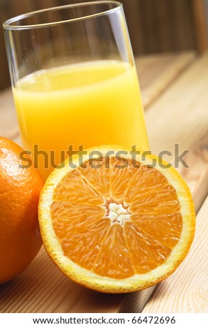 Close up of a glass of orange juice with cut and whole oranges on wooden table.