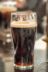 Close up of a glass of stout beer on a bar counter