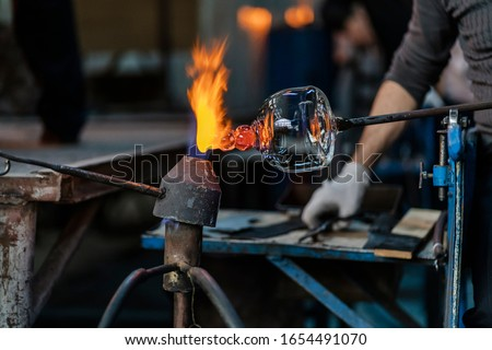 Photo of  Close-up of a glassblower artisan shaping the hot molten glass at strong fire inside his workshop. Manual glass processing by the craftsmen inside a glass factory in Transylvania, Romania.