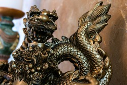 Close-up of a gold dragon sculpture, against a Venetian plaster gold wall, bokeh, February 2021.