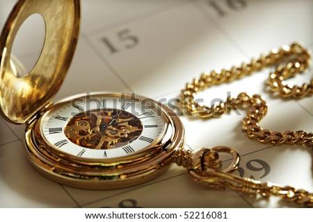 Close up of a gold pocket watch on a calendar in sunlight