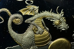 Close-up of a golden adult dragon with golden egg on a 1000 franc CFA silver coin of the Republic of Togo