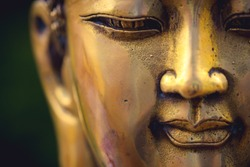 close up of a golden colored buddha head on black background ; China