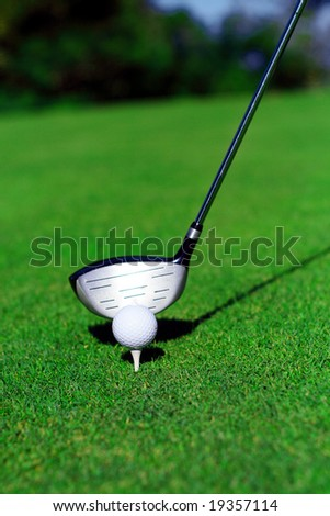 close up of a golf club, ball and tee on green grass. the golf club about to strike the ball