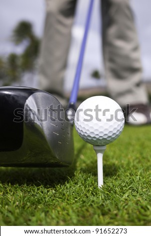 Close up of a golfer's driver with a blue shaft, ball and tee setup.
