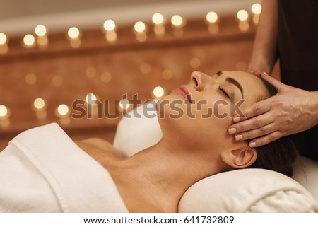 Close up of a gorgeous young woman smiling with her eyes closed enjoying head massage at spa center professional therapy health stress treatment pampering facial beauty skin recreation leisure service #641732809