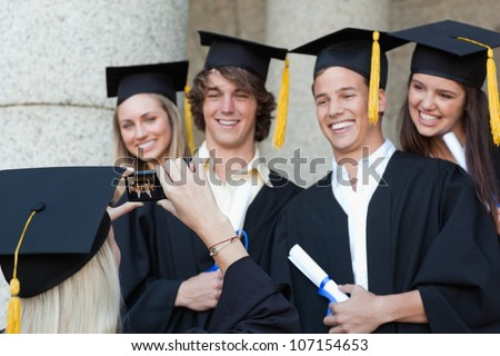 Close-up of a graduate taking a picture of her smiling friend in front of the university