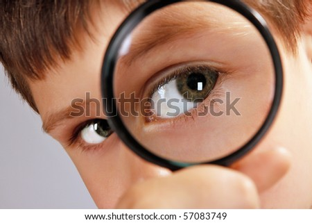 close up of a green eyed boy looking through magnifying glass