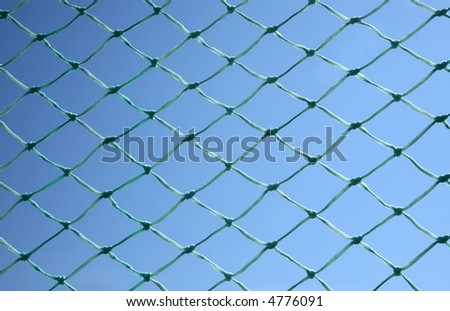 Close up of a green soccer net against a blue sky.