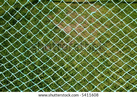 Close up of a green soccer net against with a grass background.