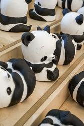Close-up of a group of ceramic graffiti panda dolls