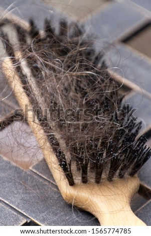 Close up of a hairbrush clogged with lost strands of thinning brown and gray hair