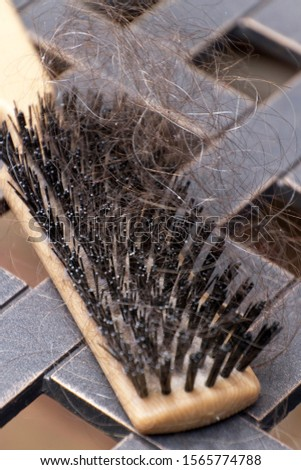 Close up of a hairbrush tangled with lost strands of thinning brown and gray hair